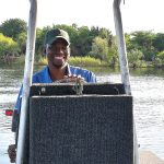 One of our guides, Tiro at the helm during a Chobe River boat safari