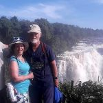 Graham and Sue in front of a section of the Victoria Falls with our local guide, Mortimer
