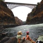 Joe and Sue looking up to the Victoria Falls bridge-border