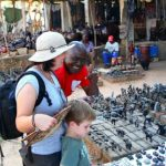 Daniella and Aiden trying their hand at bartering in the Victoria Falls curio market